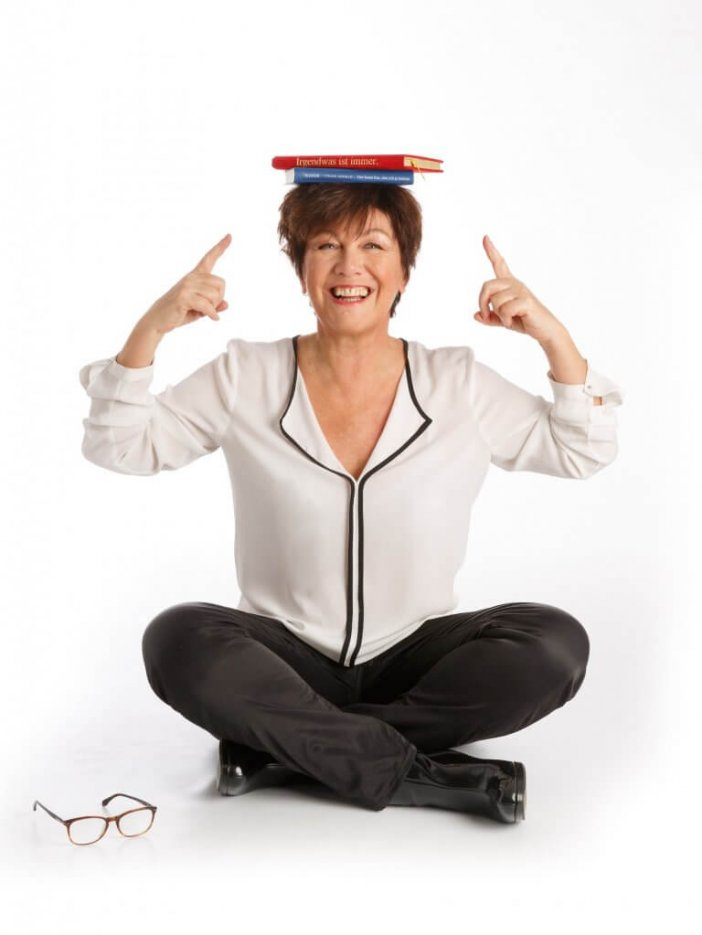 Frau sitzt am Boden mit Buch auf dem Kopf.